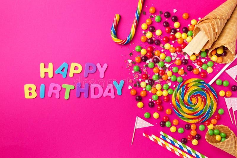 Feliz cumpleaños de los accesorios apetitosos sabrosos del partido en rosa brillante imagen de archivo