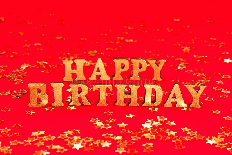 Feliz cumpleaños del texto presentado de letras del oro en fondo hermoso Confeti de oro de las estrellas foto de archivo