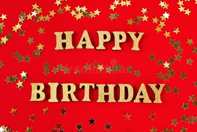 Feliz cumpleaños del texto presentado de letras del oro en fondo hermoso Confeti de oro de las estrellas imágenes de archivo libres de regalías