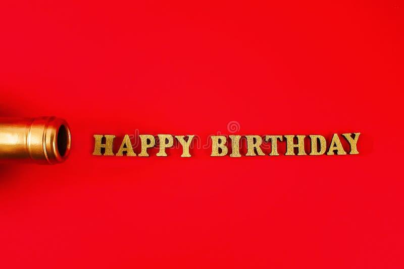 Feliz cumpleaños del texto presentado de letras del oro en fondo hermoso Cuello de oro de la botella imagenes de archivo