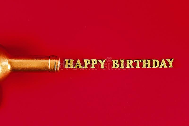 Feliz cumpleaños del texto presentado de letras del oro en fondo hermoso Cuello de oro de la botella imagen de archivo libre de regalías