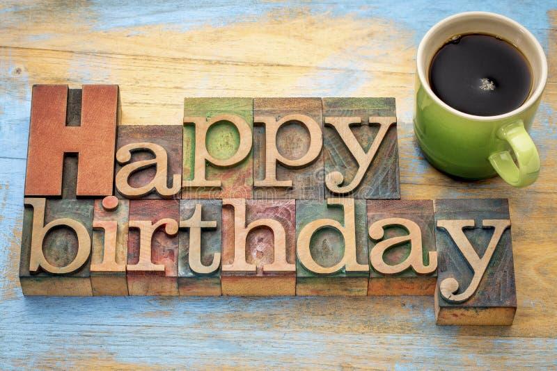 Feliz cumpleaños en el tipo de madera con café foto de archivo libre de regalías