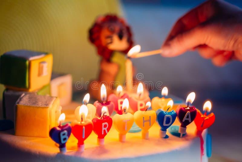 Feliz cumpleaños escrito en velas del Lit en la torta colorida Mano que lleva a cabo un partido de madera que iluminación imagenes de archivo