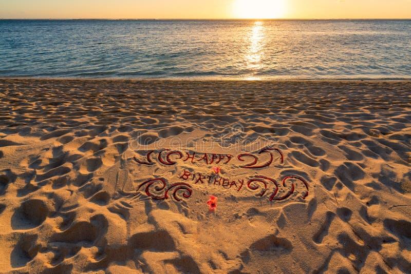 Feliz cumpleaños manuscrito en la playa de la arena imágenes de archivo libres de regalías