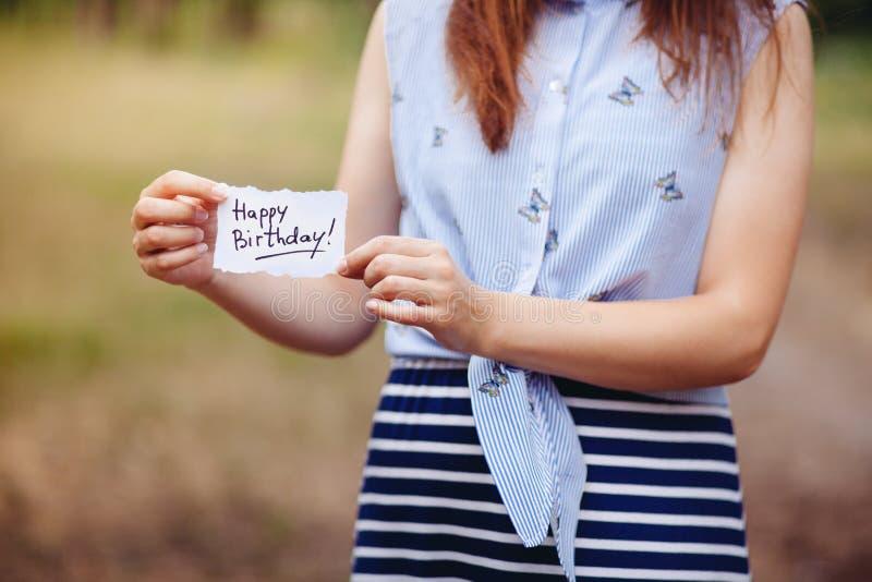 Feliz cumpleaños - mujer con la tarjeta de felicitación con el texto, concepto del aniversario imagen de archivo libre de regalías