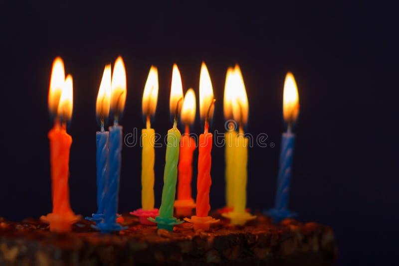 Feliz cumplea?os Brownie Cake con los cacahuetes, el caramelo salado y las velas ardientes coloridas en Violet Background Copie e foto de archivo libre de regalías