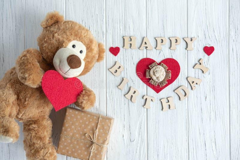 Feliz cumplea?os de la inscripci?n Oso del juguete, cajas con los regalos y cumpleaños de la inscripción congratulatoria un feliz imagenes de archivo