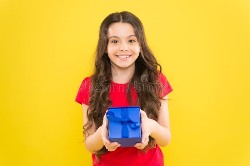 Feliz cumplea?os Muchacha del cumplea?os Regalo de cumpleaños feliz de la tenencia del pequeño niño en fondo amarillo Pequeño niñ foto de archivo