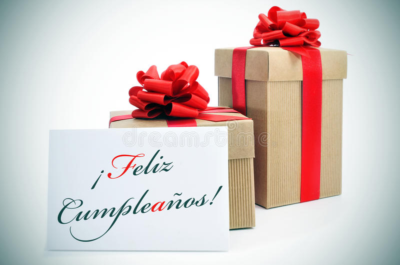 Feliz cumpleanos, happy birthday written in spanish. Some gifts and the text feliz cumpleanos, happy birthday written in spanish in a signboard stock image