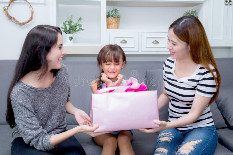Feliz de asiático y de tía de la mujer de la madre y de la hija con el regalo con la cinta rosada y la hija que besa a la madre imagenes de archivo