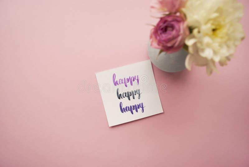` Feliz del ` escrito en estilo de la caligrafía en el papel con el ramo de rosas rosadas y de crisantemos blancos Endecha plana foto de archivo
