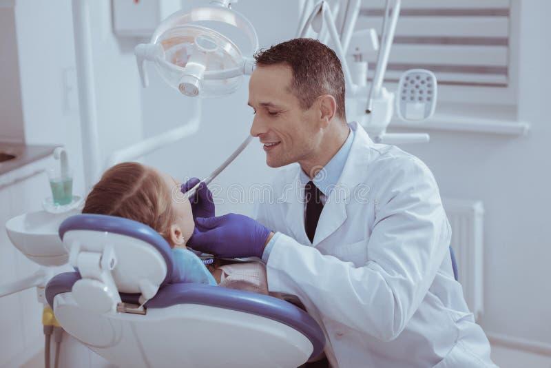 Feliz dentista de sexo masculino que explora la cavidad bucal foto de archivo