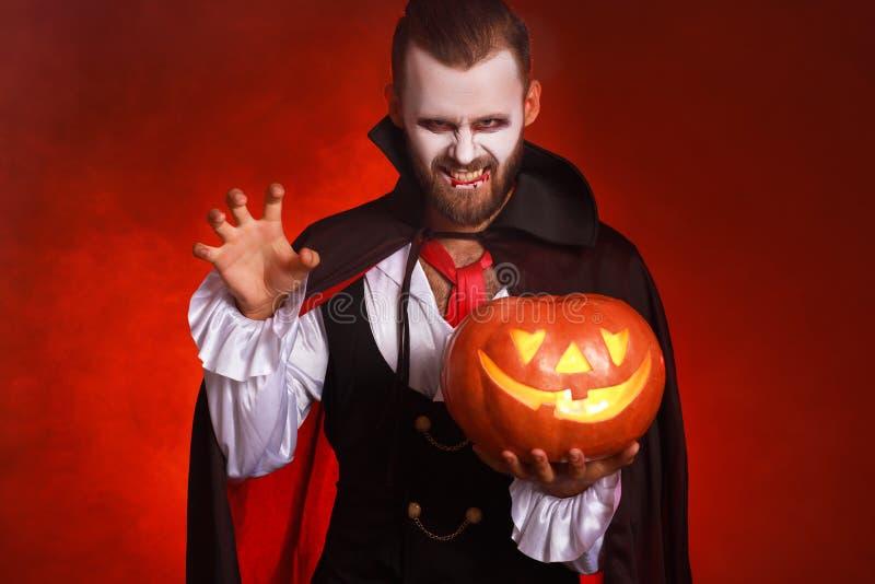 Feliz Dia das Bruxas! homem barbudo numa fantasia de vampiro de Drácula com uma abóbora sobre um fundo vermelho brilhante foto de stock