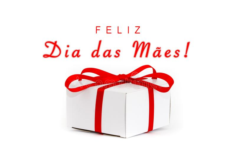 Feliz Dia das Maes in Portuguese: Happy Mothers's Day! text message and white cardboard gift box with decorative red ribbon bow stock photography