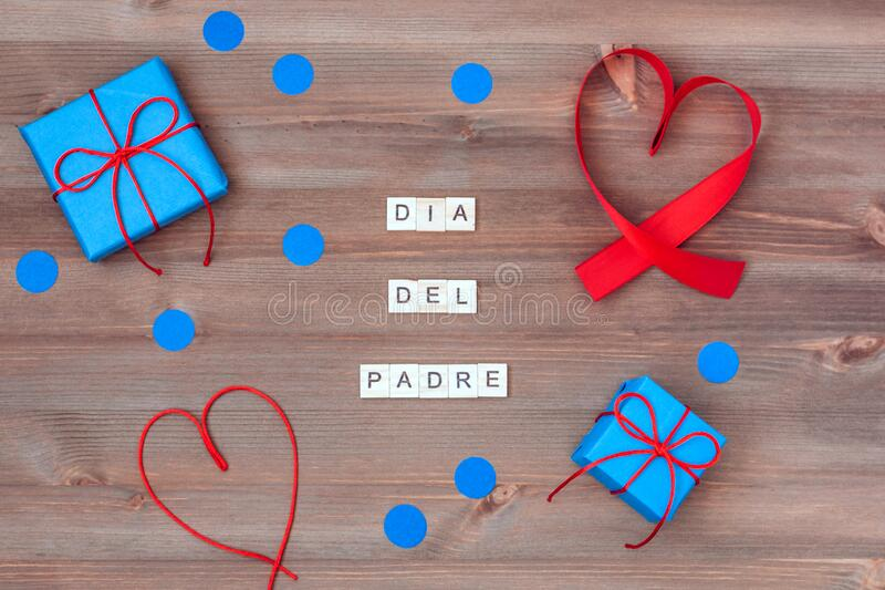 Feliz dia del padre words made of wooden blocks with blue gift boxes and red hearts on wooden background. Happy fathers day. Greeting card, holiday flat lay stock photography
