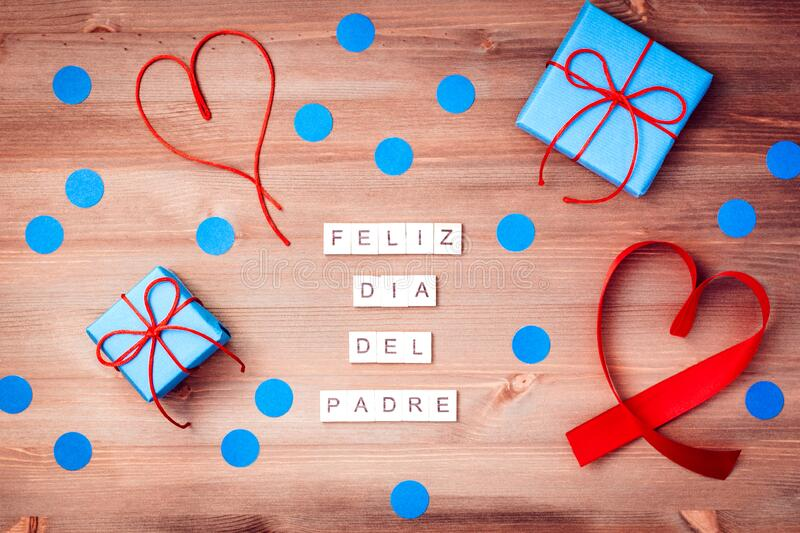 Feliz dia del padre words made of wooden blocks with blue gift boxes and red hearts on wooden background. Happy fathers day. Feliz dia del padre words that mean royalty free stock image