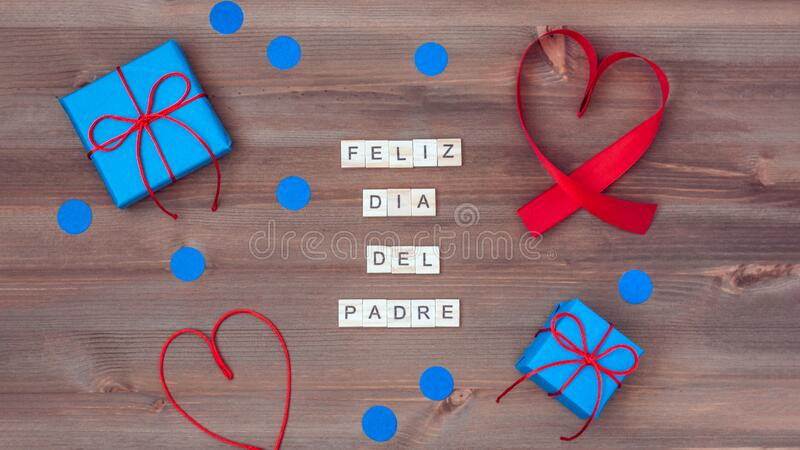 Feliz dia del padre words made of wooden blocks with blue gift boxes and red hearts on wooden background. Happy fathers day. Feliz dia del padre words that mean stock images