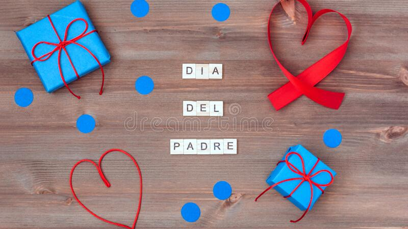 Feliz dia del padre words made of wooden blocks with blue gift boxes and red hearts on wooden background. Happy fathers day. Greeting card, holiday flat lay royalty free stock photo