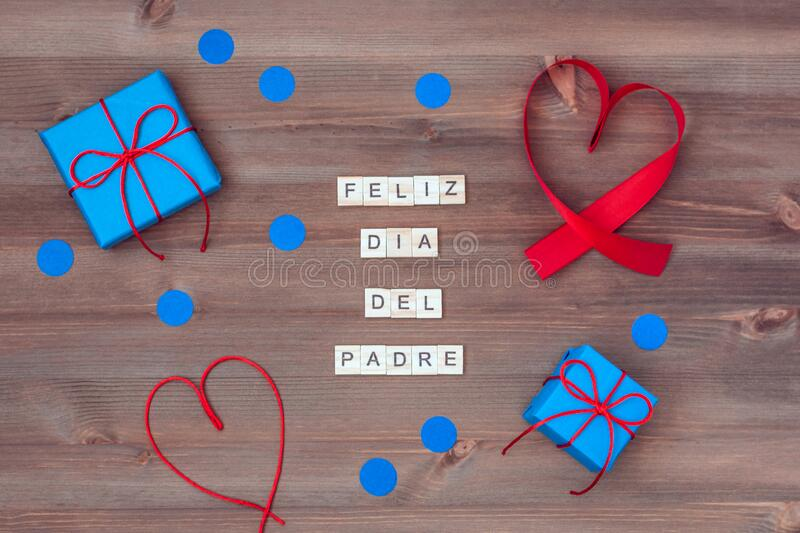 Feliz dia del padre words made of wooden blocks with blue gift boxes and red hearts on wooden background. Happy fathers day. Greeting card, holiday flat lay royalty free stock photos
