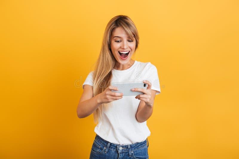 Feliz emotiva joven mujer rubia posando aislada sobre fondo amarillo vestido con una camiseta blanca casual usando teléfono móvil fotografía de archivo