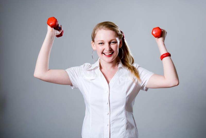 Feliz empresaria acertada con pesas de gimnasia aumentadas. fotos de archivo libres de regalías