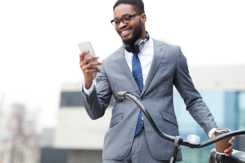 Feliz empresario afro usando teléfono, de pie con bicicleta al aire libre fotos de archivo