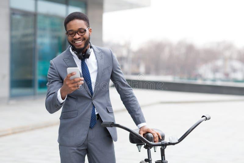Feliz empresario escribiendo por teléfono cerca de la bicicleta foto de archivo