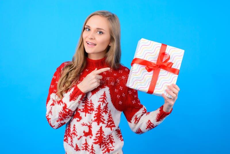 Feliz en la señora del humor de la pre-Navidad está eligiendo un presente para w foto de archivo