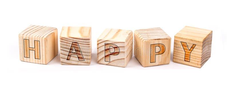 Feliz escrito en bloques de madera imagenes de archivo