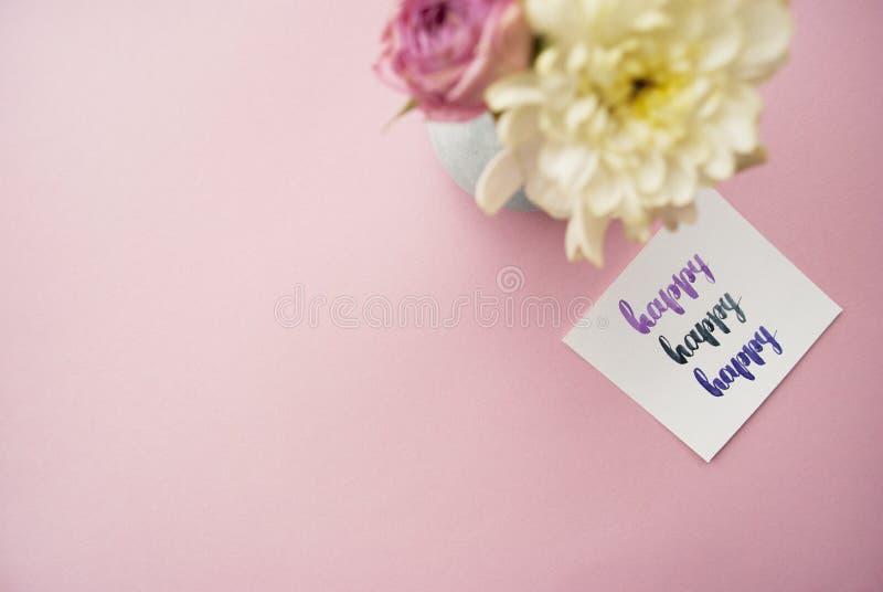 Feliz escrito en estilo de la caligrafía en el papel con el ramo de rosas rosadas y de crisantemos blancos en un fondo rosado End foto de archivo libre de regalías