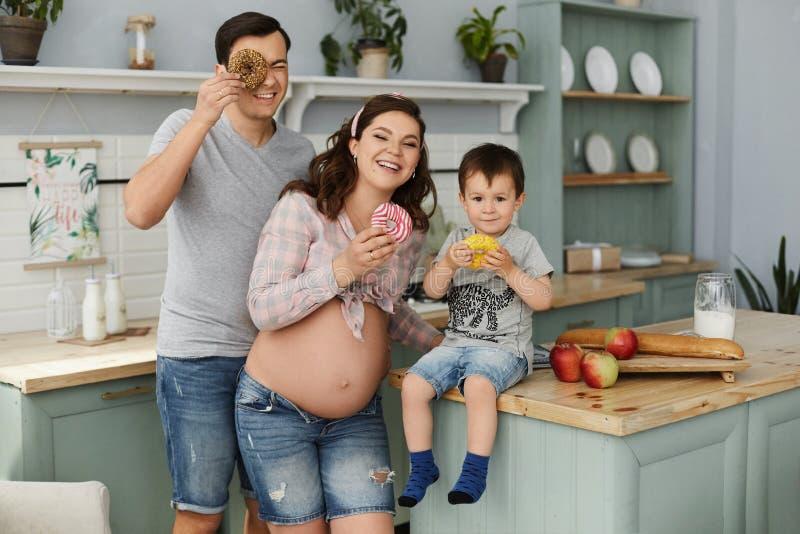 Feliz família, uma linda mulher grávida com seu homem bonito e seu bebê fazendo café da manhã e comendo saboroso imagem de stock