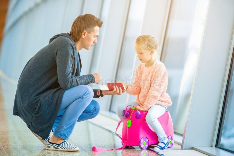 Feliz familia con dos niños en el aeropuerto que se diviertan esperando el embarque fotos de archivo libres de regalías