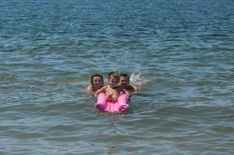 Feliz familia, mamá, papá e hija juegan en un colchón de aire nadando en el mar foto de archivo
