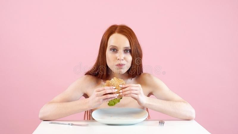 Feliz garota de cabelo vermelho quebra sua dieta e come hambúrguer Afecções musculosqueléticas e dos tecidos conjuntivos Anorexia fotografia de stock royalty free