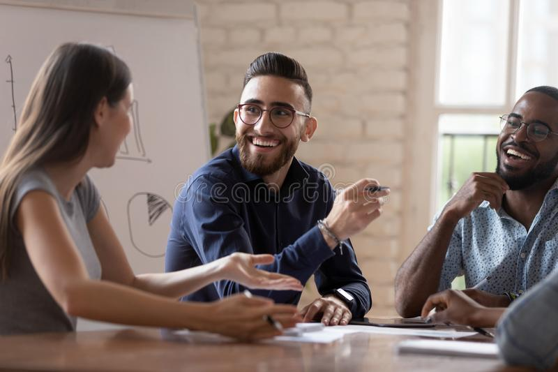 Feliz grupo de negócios criativos e diversificados conversando em reunião de grupo fotos de stock