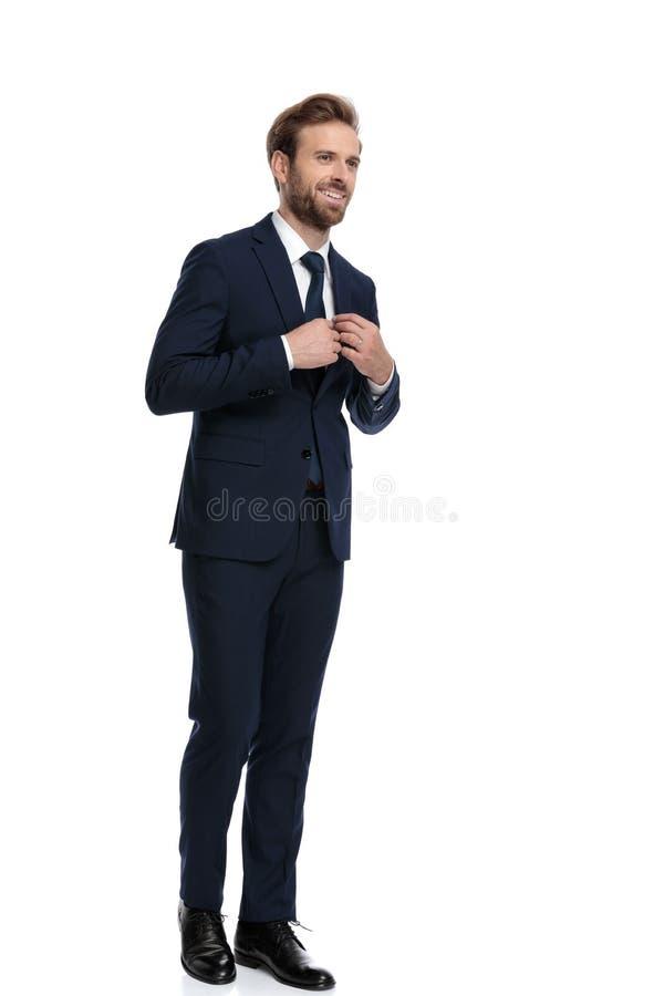 Feliz hombre de negocios con traje azul marino arreglando corbata fotos de archivo