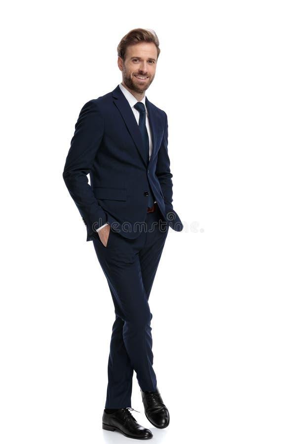 Feliz hombre de negocios con traje azul marino cogiendo la mano en los bolsillos imagenes de archivo