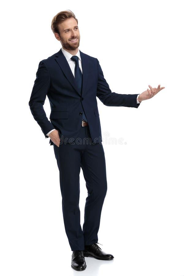 Feliz hombre de negocios sonriendo y presentándose a su lado imagen de archivo