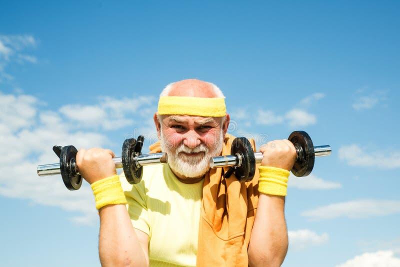 Feliz homem sênior se exercitando com o sopro do exterior Retrato do atleta do avô em fundos do céu azul foto de stock
