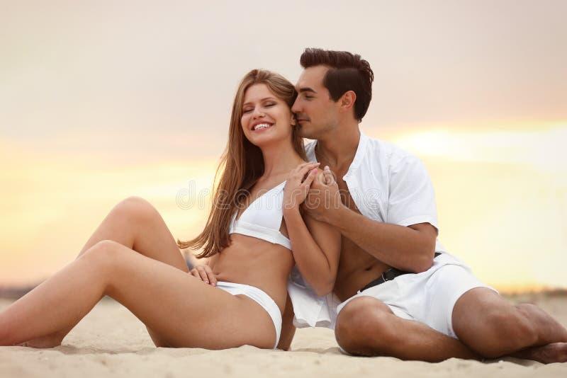 Feliz jovem casal relaxando na praia no pôr do sol imagens de stock