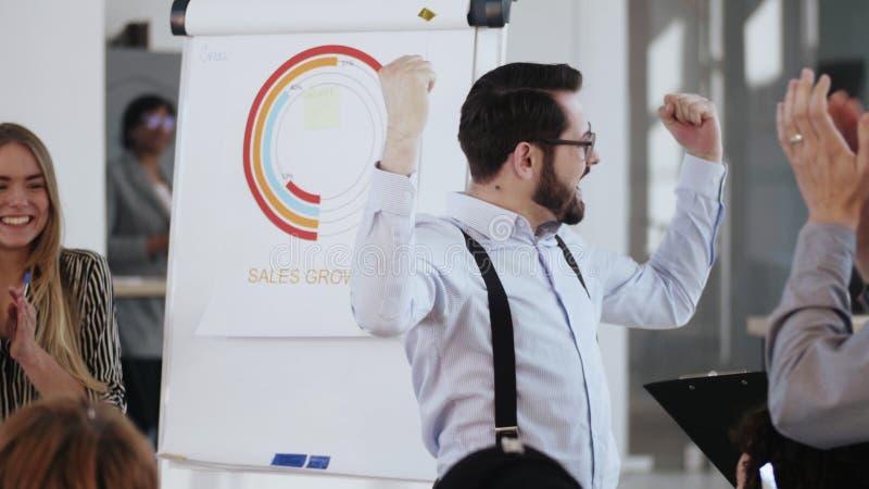 Feliz joven jefe de compañía motiva al equipo a celebrar el éxito de negocios, aplaudiendo y a los cinco, cayendo en el confetti foto de archivo