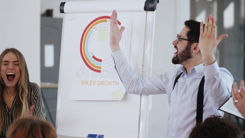 Feliz joven jefe de compañía motiva al equipo a celebrar el éxito de negocios, aplaudiendo y a los cinco, cayendo en el confetti imagenes de archivo