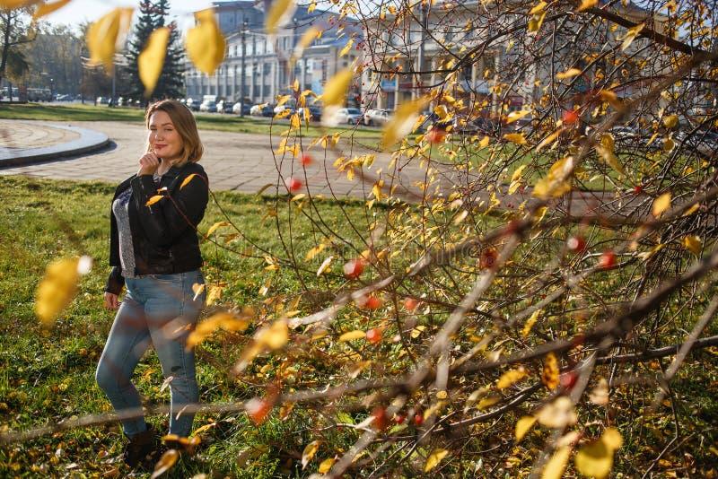 Feliz joven mujer curvada mirando al exterior en otoño. Niña disfrutando del clima cálido y soleado. Ella usa pantalones azules fotografía de archivo