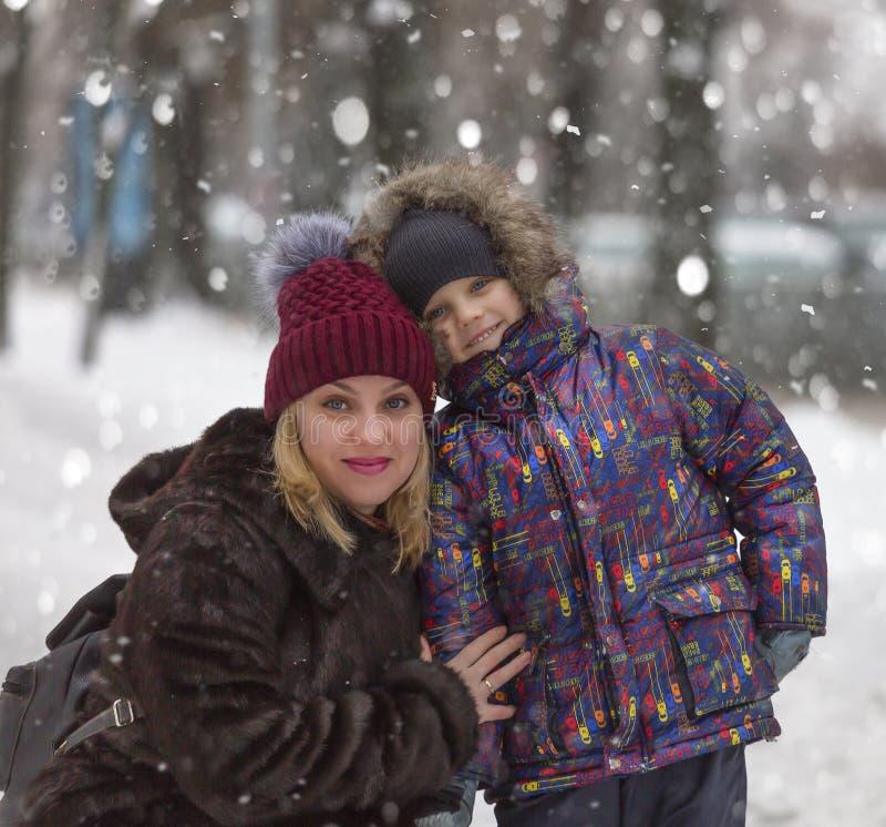 Feliz, madre, paseo, hijo, día de invierno, caídas de la nieve, Año Nuevo, la Navidad fotos de archivo libres de regalías