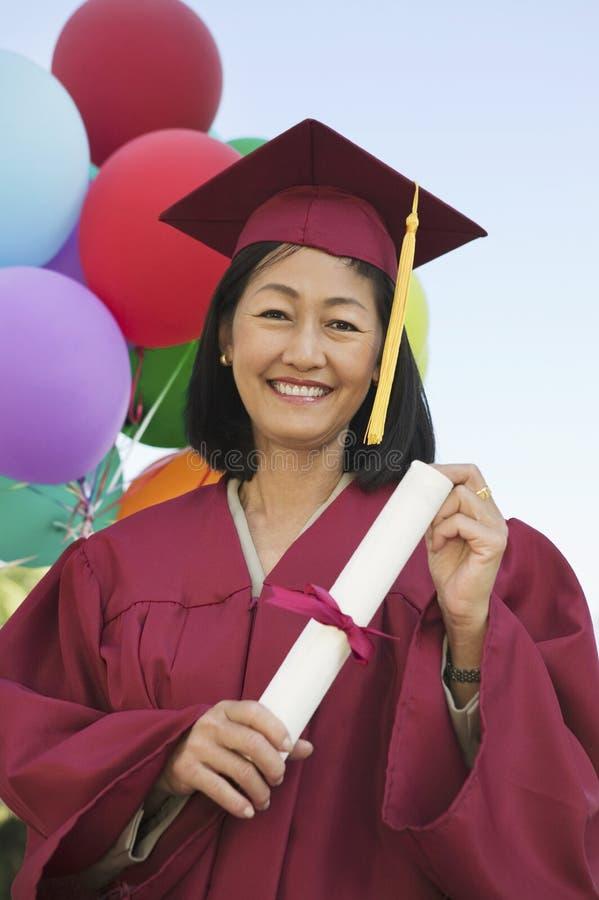 Feliz madure el grado que se sostiene graduado fotografía de archivo