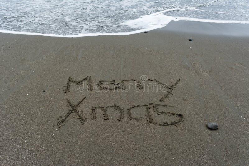 Feliz mano de Navidad escrita en la arena con el mar en el backgrou imagenes de archivo