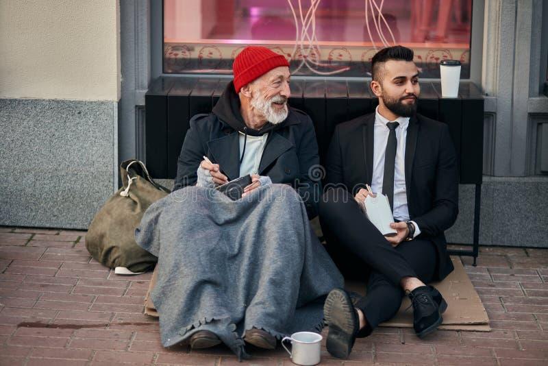 Feliz mendigo con un hombre de negocios en la calle foto de archivo