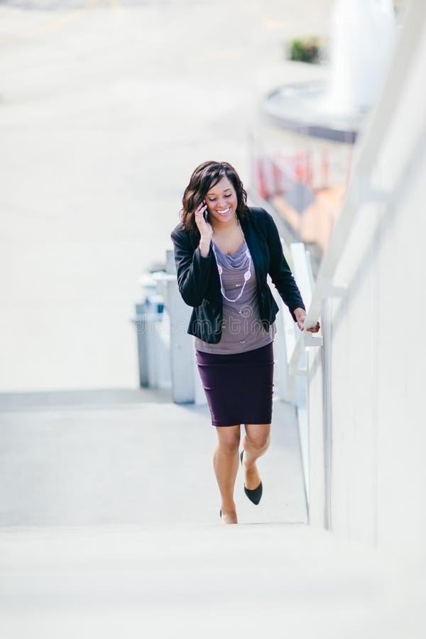 Feliz mujer de negocios afroamericana hablando por teléfono caminando por las escaleras imagenes de archivo
