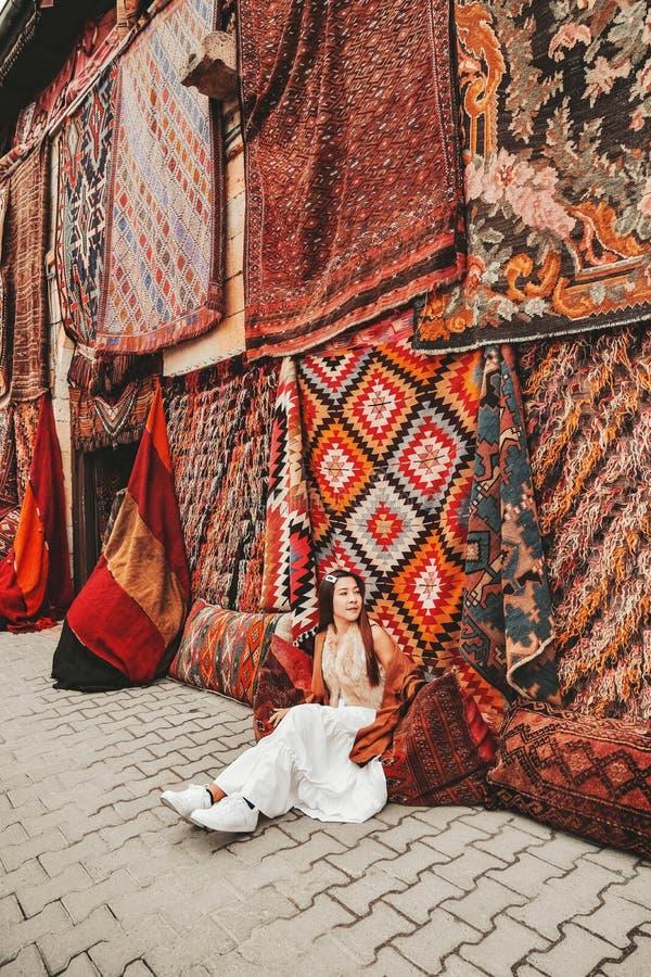 Feliz mujer viajera con asombrosas alfombras coloridas en la tienda de alfombras locales, Goreme. Cappadocia Turquía foto de archivo libre de regalías