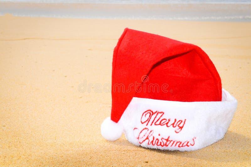 Feliz Natal com o chapéu de Santa na praia fotos de stock royalty free